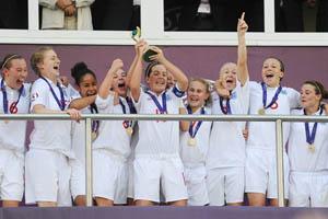 Michelle Hinnigan ergue o troféu conquistado pela Inglaterra (© UEFA)